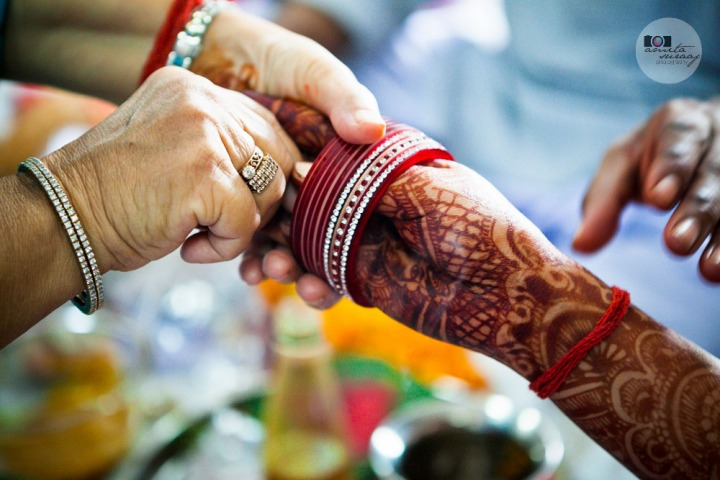 bangles being worn by the bride during the haldi ceremony