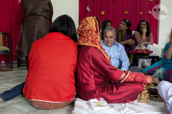 bride's friend supports her during the haldi ceremony