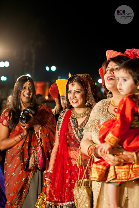 hindu bride welcoming groom with friends and family