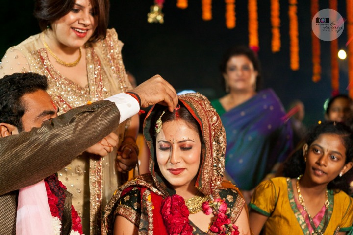 the groom applies sindoor to the bride's forehead